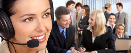 handsfree phones: Smiling  business woman with headset in the office.  Stock Photo