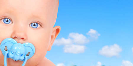 Sweet smiling baby  under blue sky photo