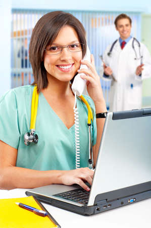 practitioner: Smiling medical nurse with telephone and laptop  Stock Photo