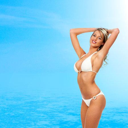 ni�as en bikini: Sexy mujer rubia, cielo azul y el azul del agua Foto de archivo