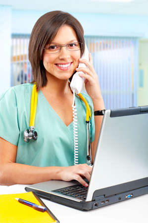 Smiling medical nurse with telephone and laptop Stock Photo - 4939460