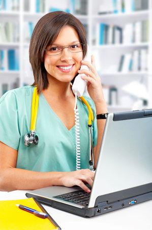 Smiling medical nurse with telephone and laptop Reklamní fotografie