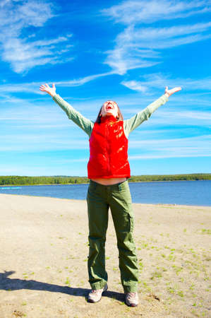 Young happy smiling woman under blue sky