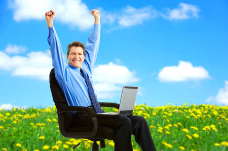 Successful happy businessman with laptop under blue sky.   photo