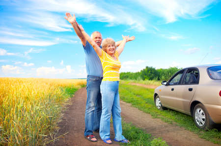Smiling happy elderly couple, car, nature