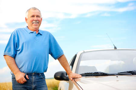 Smiling happy elderly man  and a new car