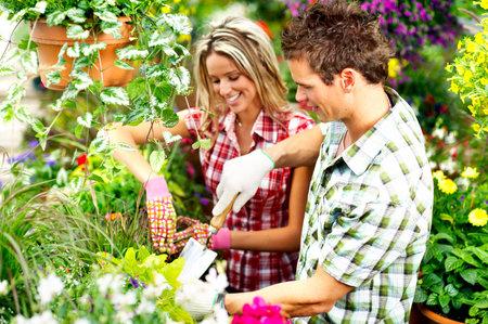 famiglia in giardino: Fioristi giovane sorridente persone al lavoro nel giardino