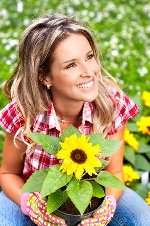 工作在庭院里的年轻微笑的妇女卖花人