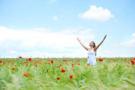 woman praying: Beautiful young happy woman under blue sky.   Stock Photo