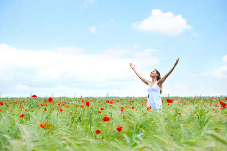 mujer orando: Joven y bella mujer feliz bajo el cielo azul.