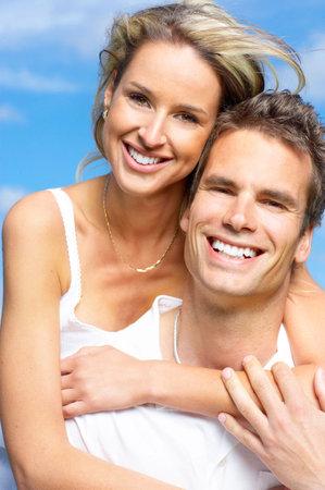 pareja abrazada: Pareja joven sonriente amor bajo el cielo azul Foto de archivo