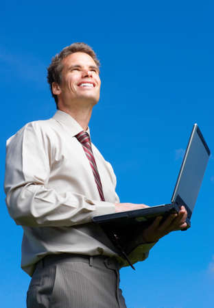 Happy successful  businessman with laptop   under blue sky.   photo