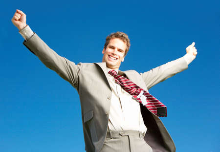 Successful happy businessman under blue sky.   photo