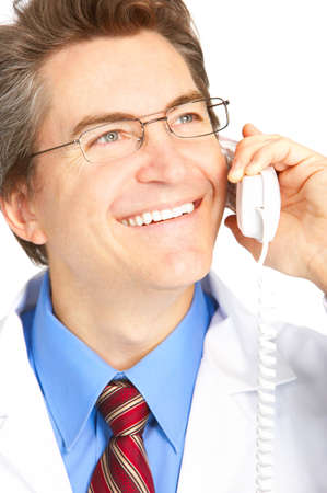 Smiling medical doctor calling by phone. Over white background  photo