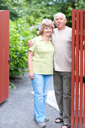 Smiling happy elderly couple near the home