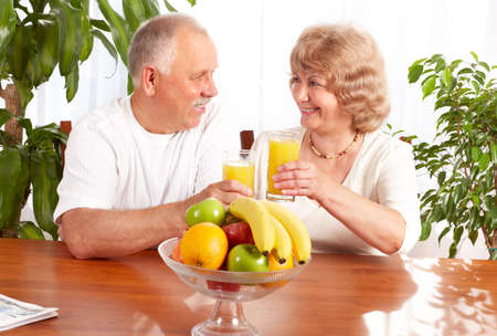 Happy elderly couple with fresh fruits.   photo