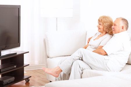 幸せな老夫婦の家でテレビを見て笑みを浮かべて