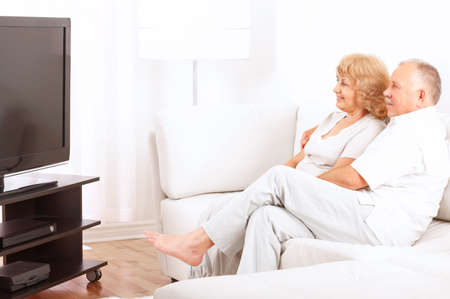 Happy smiling elderly couple watching TV at home 스톡 콘텐츠