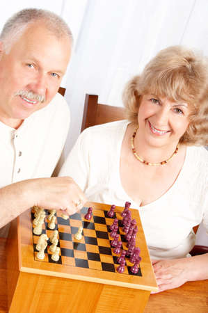 Happy smiling elderly couple playing chess at home  photo