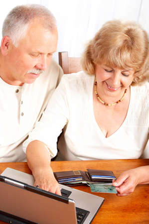 Happy smiling elderly couple working with laptop at home Stock Photo - 5349701