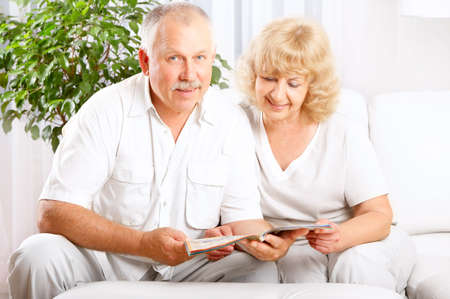 newspaper read: Happy smiling elderly couple reading a magazine  at home  Stock Photo