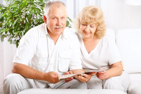 adult magazines: Happy smiling elderly couple reading a magazine  at home  Stock Photo