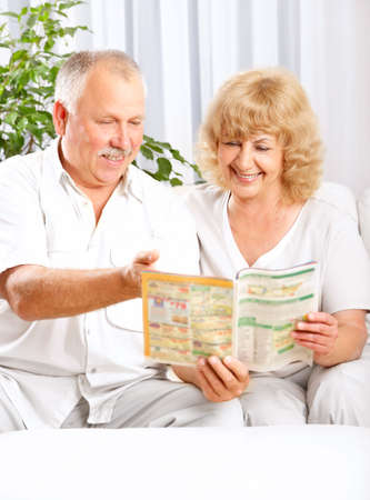 Happy smiling elderly couple reading a magazine  at home  photo