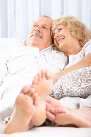 couple on couch: Happy smiling elderly couple at home
