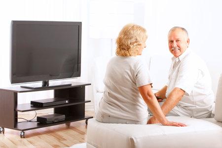 Sonriendo feliz pareja de ancianos en casa viendo la televisión
