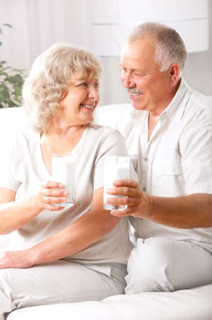 Happy elderly couple drinking milk at home  Reklamní fotografie