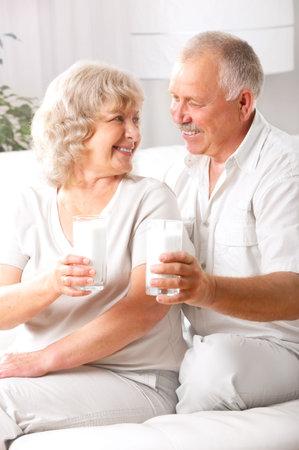 woman drinking milk: Happy elderly couple drinking milk at home  Stock Photo
