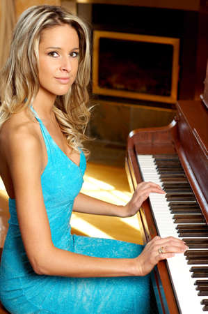 Smiling  blonde woman playing the piano  Stock fotó