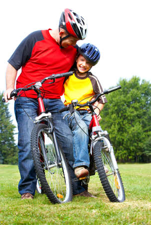 Happy family. Father and son riding  in the park Stock Photo - 5487334