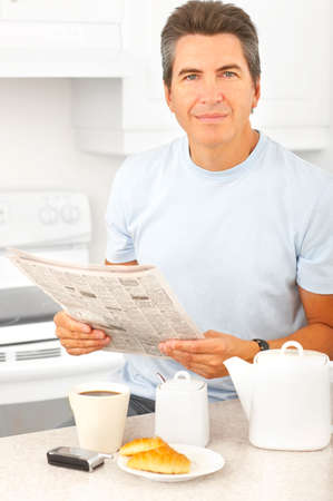 Young smiling man having lunch in  kitchen  Imagens