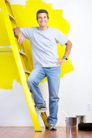 glimlachende knappe man in de buurt van de geschilderde binnenmuur van thuis.