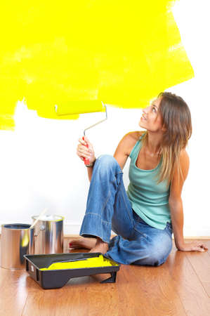 smiling beautiful woman painting interior wall of home.   Imagens