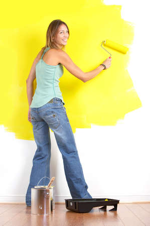smiling beautiful woman painting interior wall of home.   Stock Photo