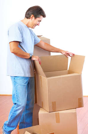 settler: Handsome man  with boxes  in the new apartment after moving  Stock Photo