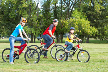 woman bike: Happy family. Father, mother and son riding  in the park