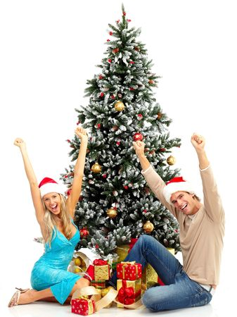 Young happy couple near  a Christmas tree. Isolated over white background Stock Photo - 5662838