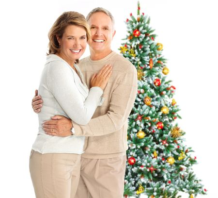 Elderly  happy couple near a Christmas tree. Isolated over white background Stock Photo - 5662836