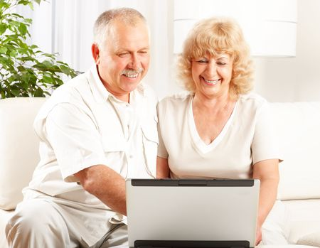 Happy smiling elderly couple working with laptop at home  photo