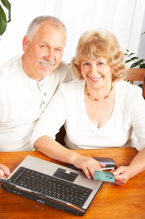 Happy smiling elderly couple working with laptop at home Stock Photo - 5713655