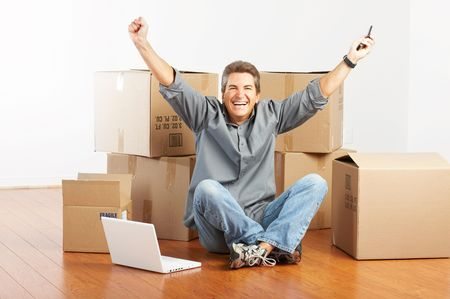 house call: Handsome man  with boxes  in the new apartment after moving