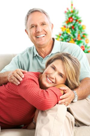 Ouderen gelukkige paar in de buurt van een kerstboom. Isolated over white background Stockfoto
