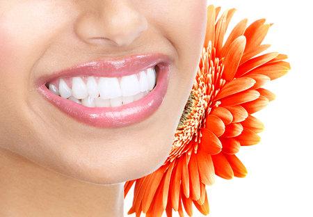 Mooie jonge vrouw tanden en bloem. Geïsoleerd op witte achtergrond