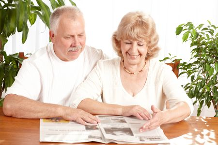 old people: senior couple reading a magazine  at home  Stock Photo