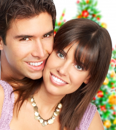 Young happy couple near  a Christmas tree. Over white background photo