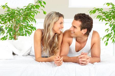 Jonge gelukkige paar in een bed thuis