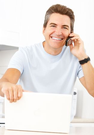 Young smiling man working with laptop in  kitchen  photo